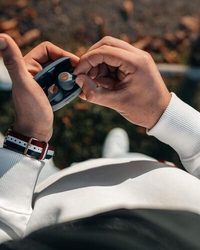 Homme en extérieur prenant ses écouteurs Jabra Elite Active 65t de son boitier
