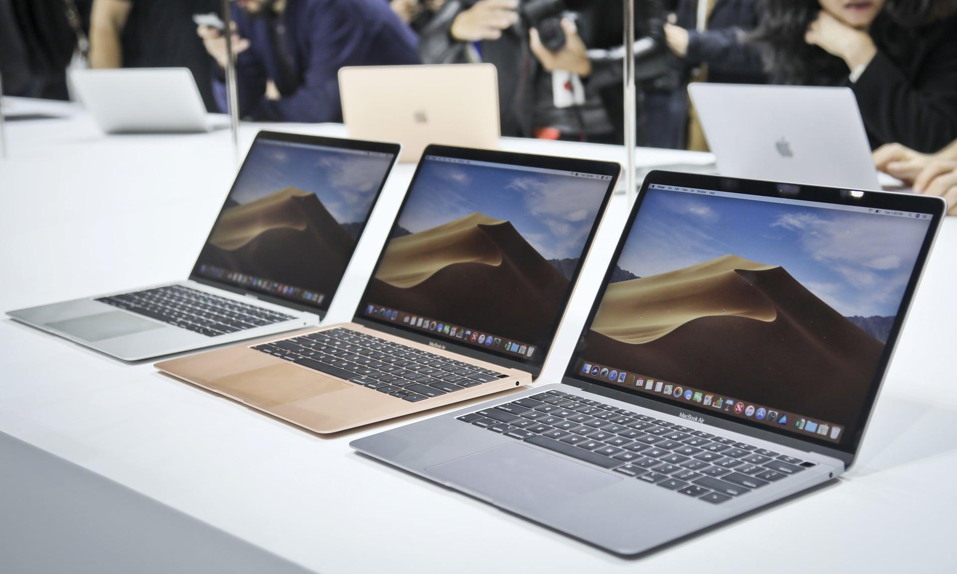 assortiment de macbooks air dans un apple store avec personnes en fond